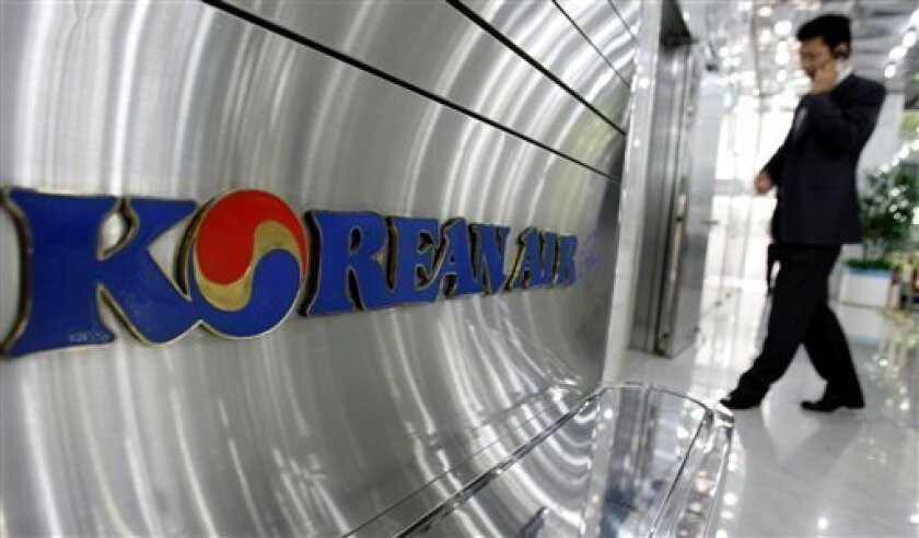 A South Korean man uses his mobile phone at a showroom of the headquarters of Korean Air Co. in Seoul, South Korea, Thursday, May 7, 2009. Korean Air Lines Co. said Thursday its first quarter net loss widened as weakness in the South Korean won drove up costs denominated in dollars. (AP Photo/ Lee Jin-man)