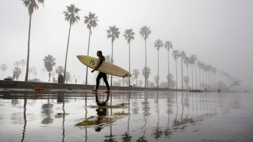 Gil Vargas gets out of the water after surfing at La Jolla Shores as thick fog envelopes the coast.