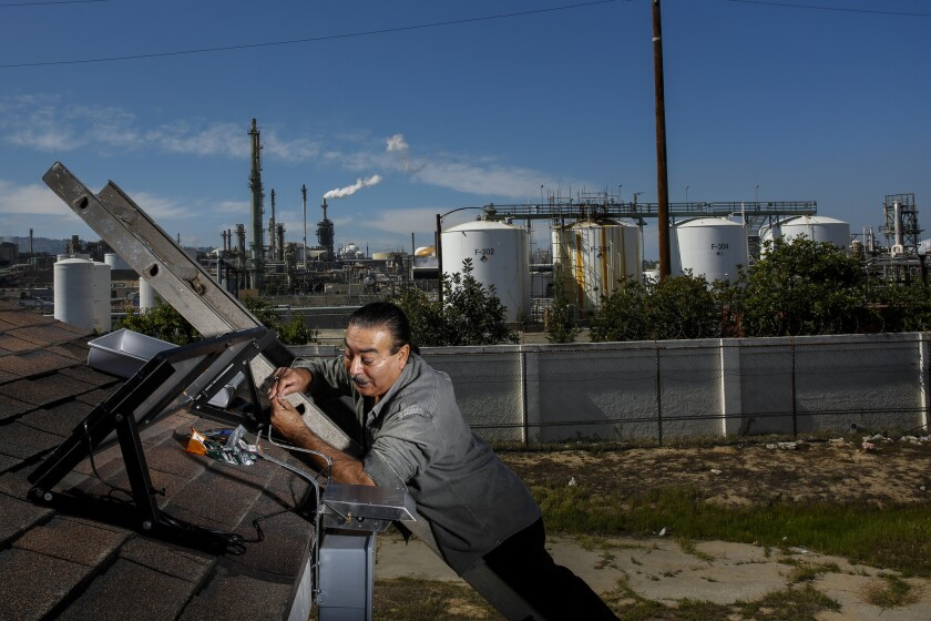 Jesse Marquez, executive director of Coalition for a Safe Environment, installs an pollution-monitoring device on a Wilmington home near the Phillips 66 oil refinery.