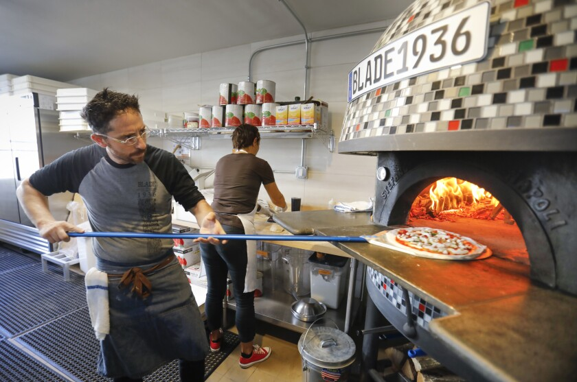 John Carlo Ferraiuolo, general manager and partner at the new Italian restaurant Blade 1936 in Oceanside, in the original Blade-Tribune and News building makes a Margherita pizza.Photographed September 24, 2019, in Oceanside, California.