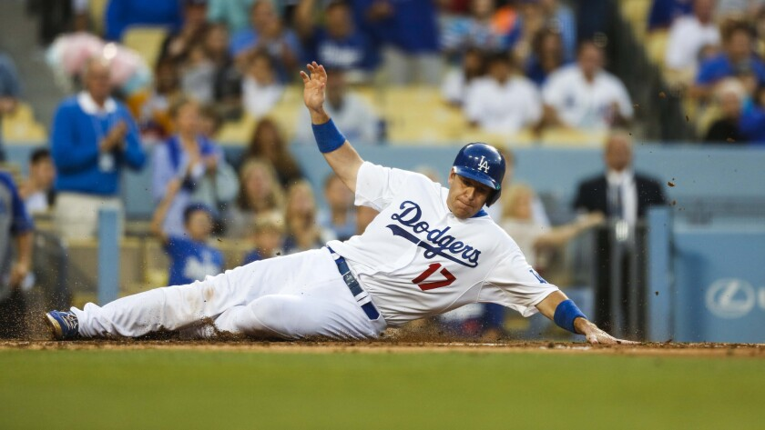 Dodgers catcher A.J. Ellis slides into home plate to score during a game against the St. Louis Cardinals in June.