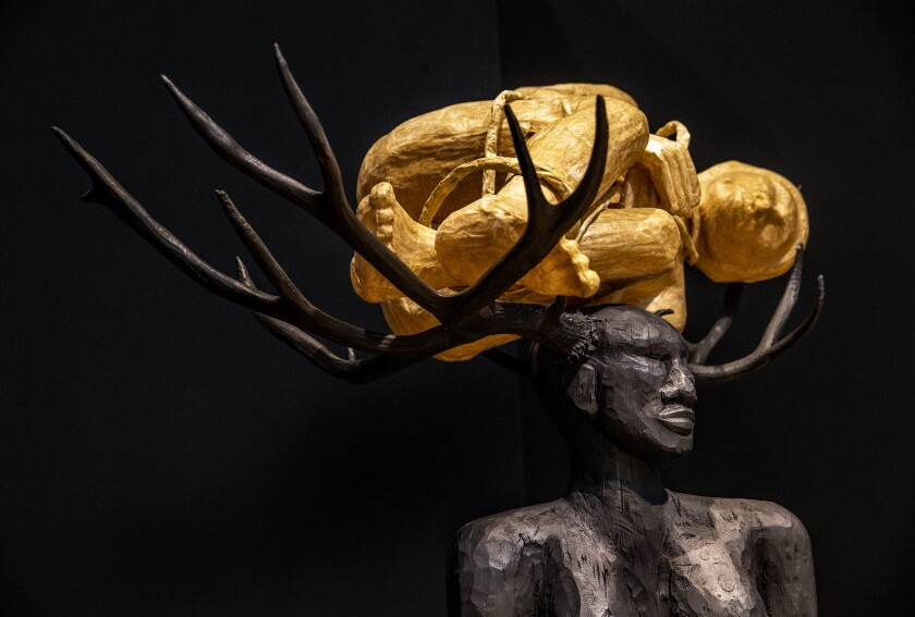 A Black female figure with antlers is shown in profile, her antlers bearing a bound figure made from blond wood