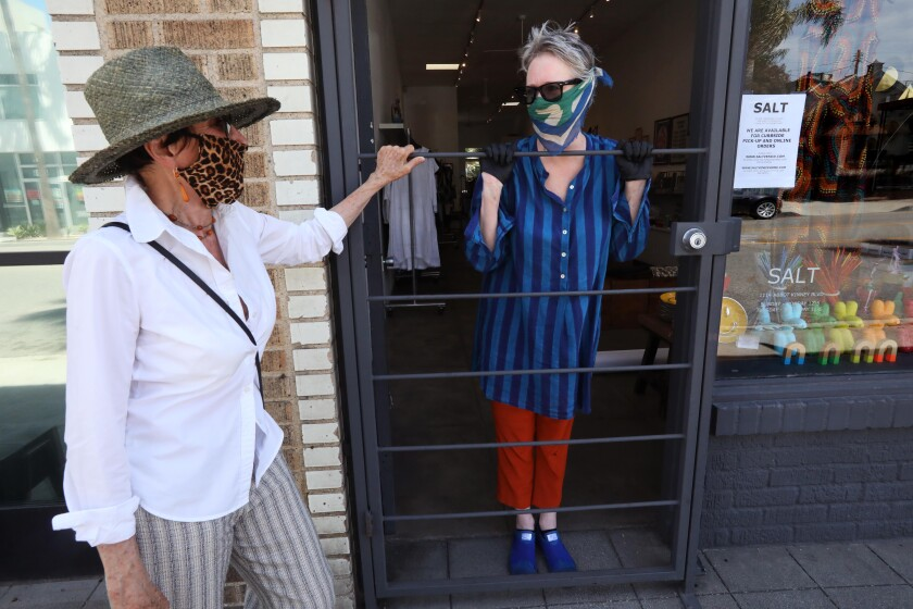 Shopper Enid Koffler, left, talks to owner Holly Boies on Thursday at Salt, a women's clothing store in Venice. Boies is planning to reopen her store on Friday for curbside pickup.