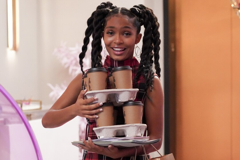 "Yara Shahidi holds three trays of paper coffee cups in ""Grown-ish."""