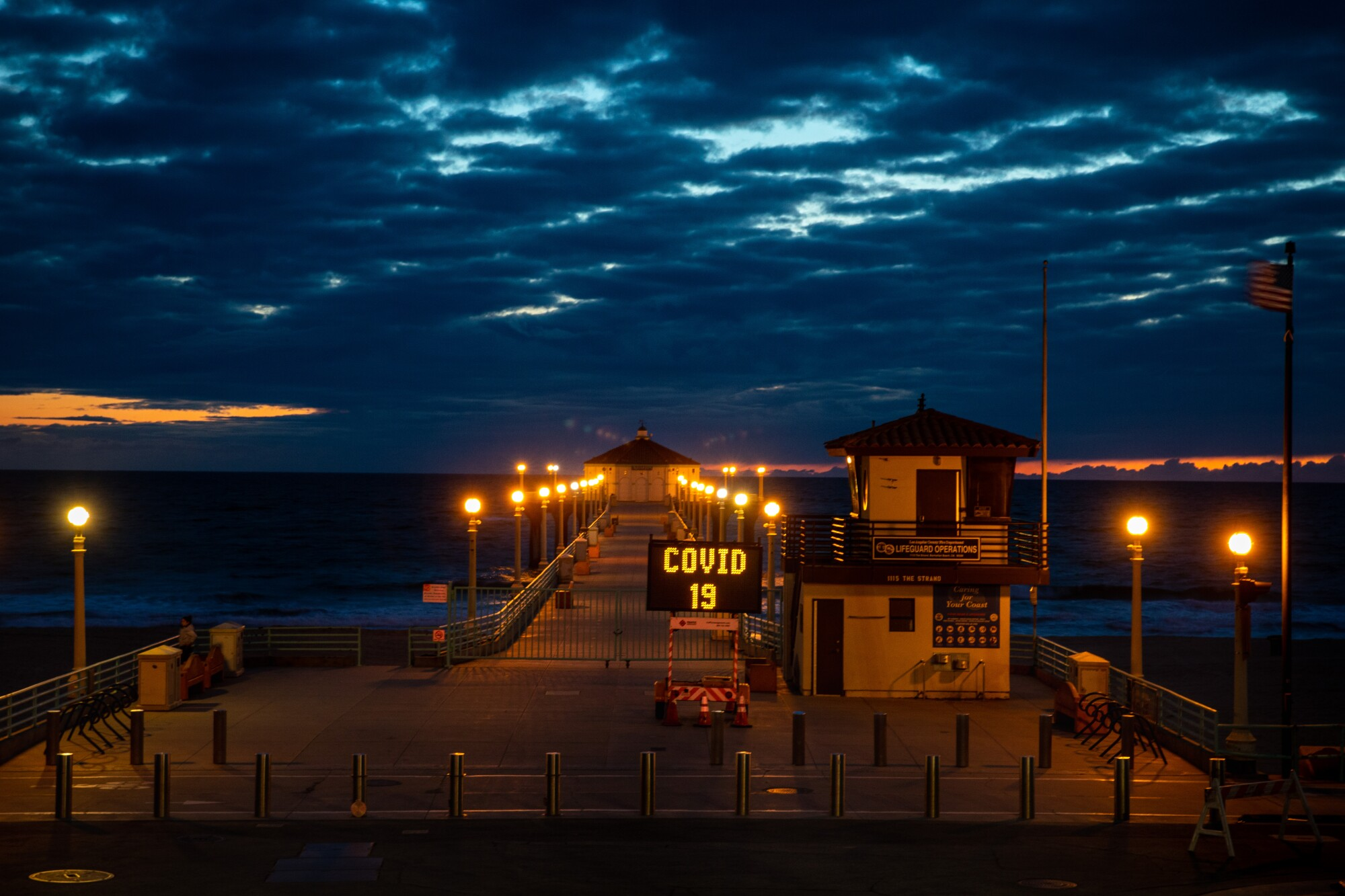 """The Manhattan Beach Pier is locked, and a city sign explains why in three repeated messages: """"Lot closed,"""" """"COVID-19"""" and """"Social Distancing."""""""