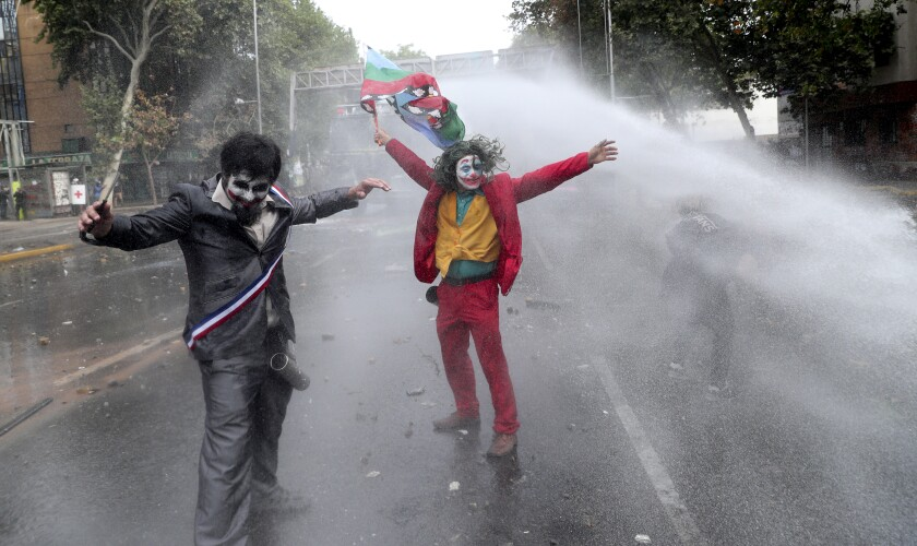 """Men dressed as clowns, one dressed as the the movie character """"The Joker"""" flying a Mapuche indigenous flag, are sprayed by a police water cannon during an anti-government protest in Santiago, Chile, Monday, Nov. 4, 2019. Chile has been facing weeks of unrest, triggered by a relatively minor increase in subway fares. The protests have shaken a nation noted for economic stability over the past decades, which has seen steadily declining poverty despite persistent high rates of inequality. (AP Photo/Esteban Felix)"""