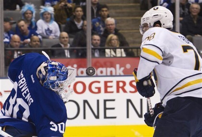 Toronto Maple Leafs goalie Ben Scrivens, left, make a save as Buffalo Sabres forward Corey Tropp, right, watches the puck during the first period of an NHL hockey game in Toronto on Saturday, March 31, 2012. (AP Photo/The Canadian Press, Nathan Denette)