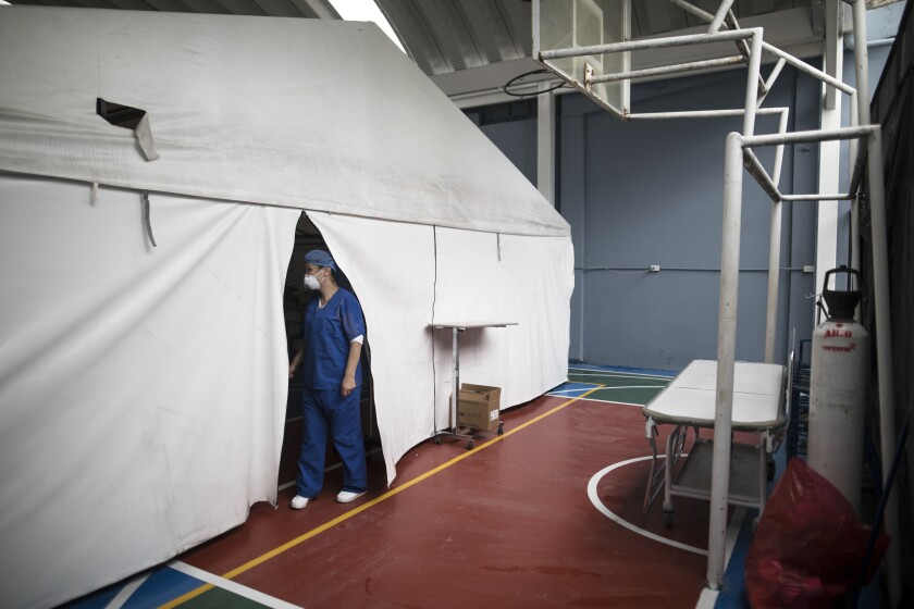 A healthcare worker tends to COVID-19 patients resting inside a tent set up on a soccer court of the Samaritana Hospital to accommodate the increased numbers in patients infected with the virus, in Bogota, Colombia, Thursday, June 3, 2021. Colombia has become a pandemic hotspot experiencing a third wave of COVID-19 infections and a surge in deaths. (AP Photo/Ivan Valencia)