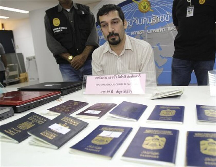 Iraqi national Raihan Ashour Oraibi Alfatlawi sits behind false passports he had possessed as he is presented to the media at Thai Immigration headquarter in Bangkok, Thailand, Tuesday, March 27, 2012. Thai police arrested Alfatlawi and a Thai woman on Tuesday, while Australian police announced the arrest of four men in Sydney and Melbourne in a multination operation against human trafficking networks. (AP Photo/Sakchai Lalit)