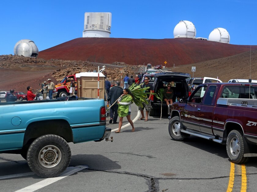 Protesters block vehicles from getting to the Thirty Meter Telescope groundbreaking ceremony site at Mauna Kea, Hawaii on Tuesday, Oct. 7, 2014. Protesters halted a groundbreaking and Hawaiian blessing ceremony for the construction of one of the world's largest telescopes. (AP Photo/Hawaii Tribune-Herald, Hollyn Johnson)