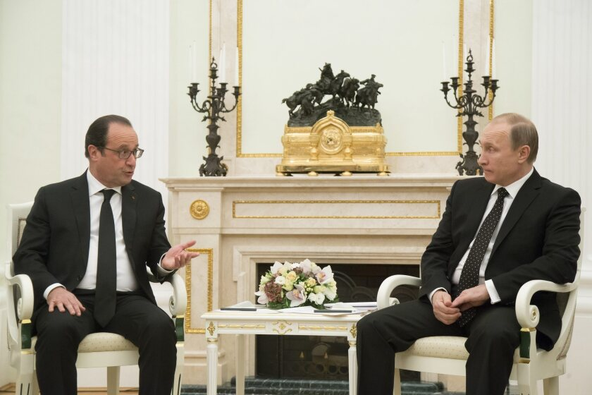 Russian President Vladimir Putin, right, speaks with French President Francois Hollande during their meeting in Moscow on Nov. 26.