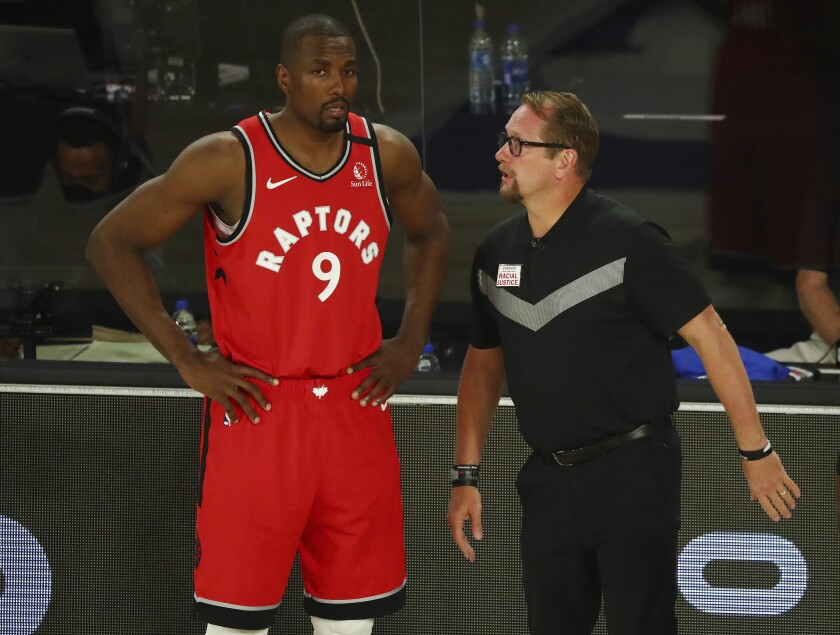 Serge Ibaka listens to Toronto coach Nick Nurse during a playoff game against Brooklyn on Aug. 23, 2020, in Orlando, Fla.