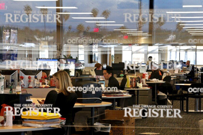 People work at computers inside the Orange County Register newsroom.