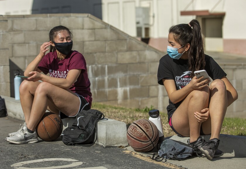 Two masked girls sit outside a school with basketballs.