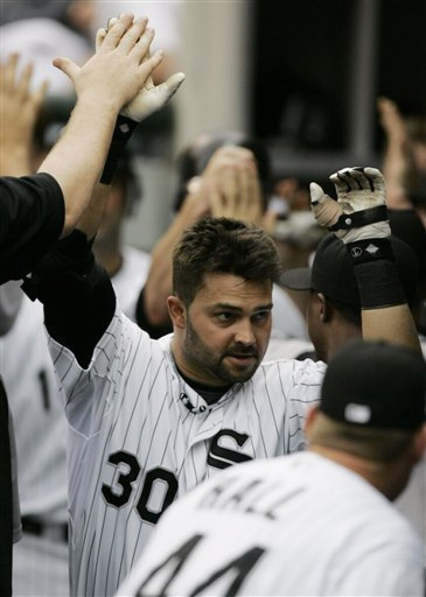 Chicago White Soxs' Nick Swisher celebrates in the dugout after hitting a three-run home run against the Minnesota Twins during the second inning of a baseball game Sunday, June 8, 2008 in Chicago. (AP Photo/M. Spencer Green)