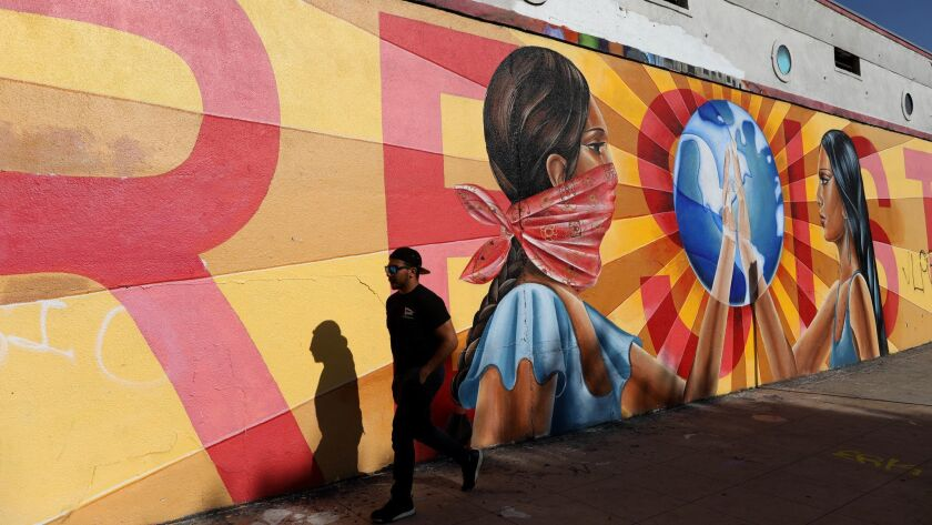 """A man walks past a mural on Anderson Street in Boyle Heights that reads """"RESIST."""""""