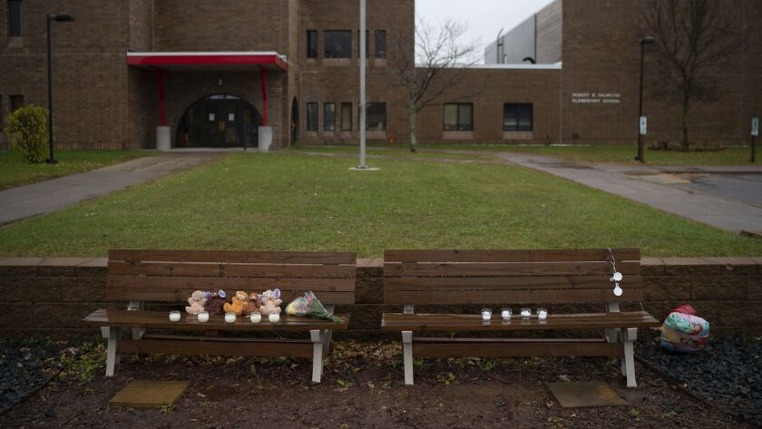 Teddy bears, flowers, and candles were placed on benches outside Halmstad Elementary School in Chipp