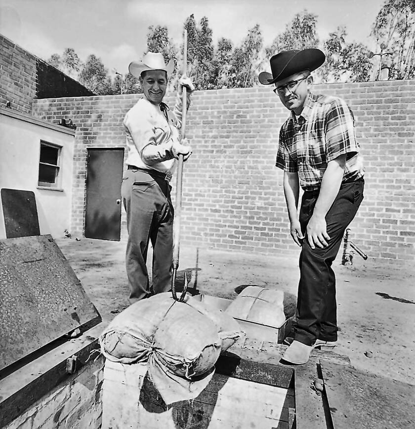 In this 1967 photo, Brother Lawrence Sandstrom, right, supervises as Emile Jacobs lowers meat into a pit at Rancho San Antonio, a Chatsworth group home run by the Brothers of Holy Cross religious order. The religious order's confidental files on Sandstrom, who resigned from the order in 1997, could become public as early as this month.