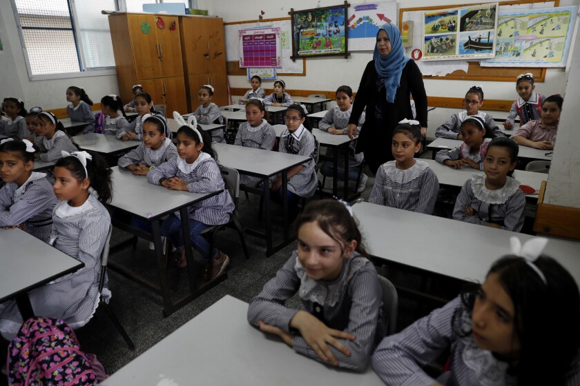 Students sit at their class on the first day of the new school year at the United-Nation run Elementary School at the Shati refugee camp in Gaza City, Saturday, Aug. 8, 2020. Schools run by both Palestinian government and the U.N. Refugee and Works Agency (UNRWA) have opened almost normally in the Gaza Strip after five months in which no cases of community transmission of the coronavirus had been recorded. (AP Photo/Adel Hana)