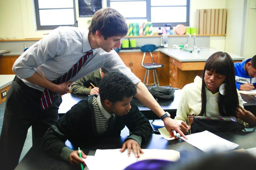 Physics teacher, Evan Dvorak, leans into to explain a class assignment to Imani Earl a senior at Jordan High School.