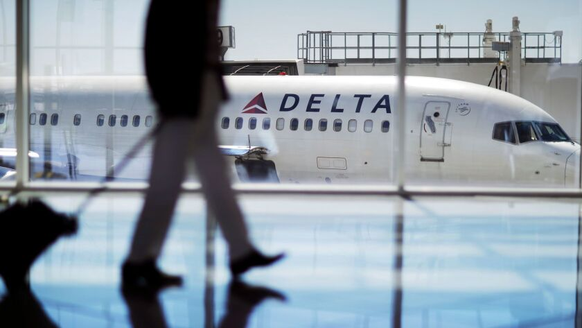 A Delta Air Lines jet sits at a gate at Hartsfield-Jackson International Airport in Atlanta. Delta and United Airlines said Saturday they are cutting ties with the National Rifle Assn.