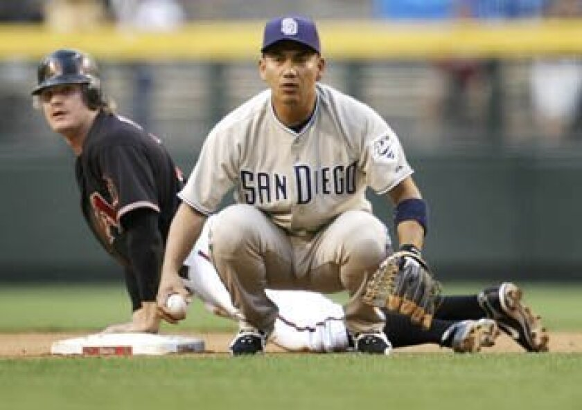 Arizona Diamondbacks' Eric Byrnes, rear, and the Padres' Tadahito Iguchi watch the play at third on a double steal during the first inning Saturday in Phoenix. Byrnes was safe on the play. AP Photo/Matt York