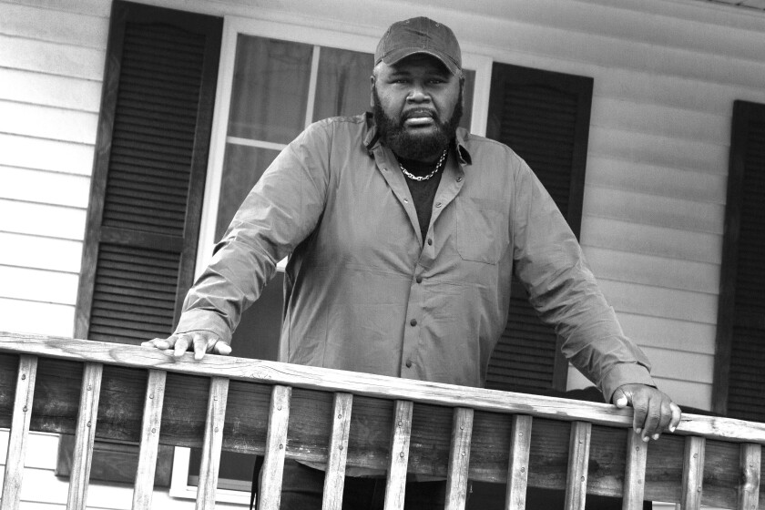 A man with his hands on porch railing