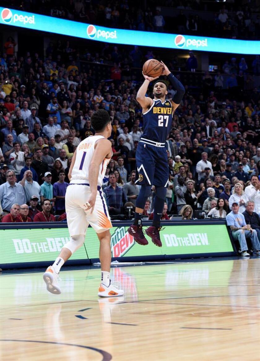 El jugador de los Nuggets Jamal Murray (d) en acción ante Devin Booker (i) de los Suns durante un juego. EFE/Archivo