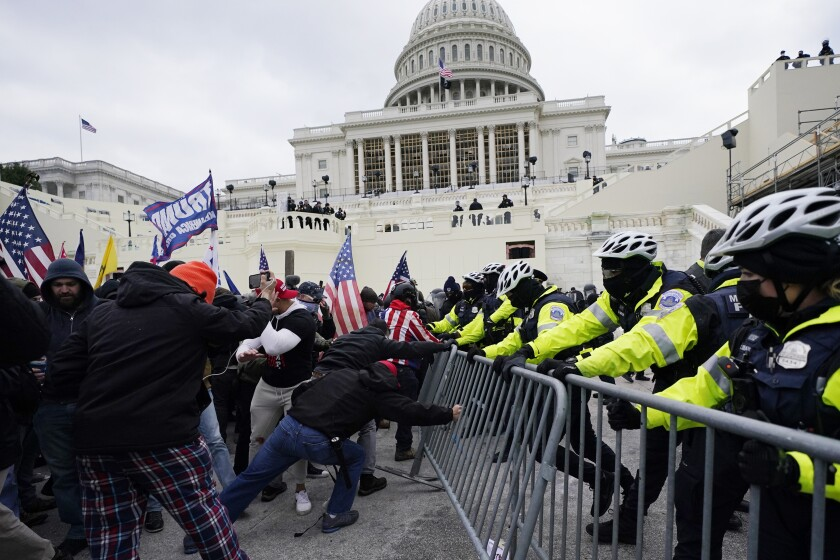 People with U.S. and Trump flags shove against a metal barrier as a line of police tries to hold them back.