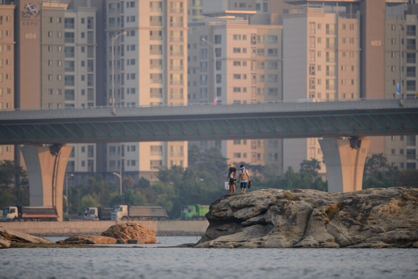 A couple walks along the harbor in Songdo