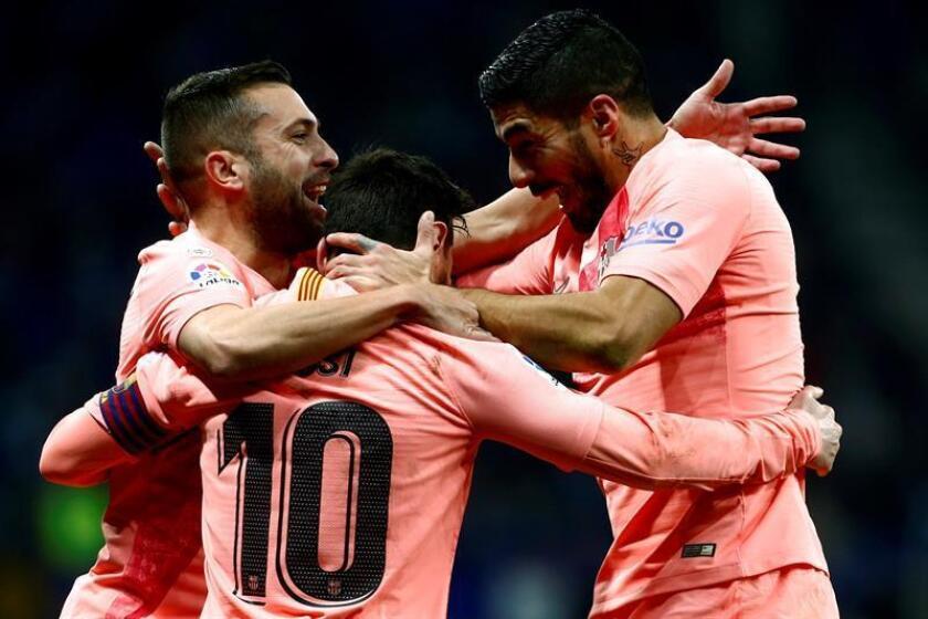 El delantero argentino del FC Barcelona Leo Messi (c) celebra con Jordi Alba (i) y el uruguayo Luis Suárez (d) su gol, primero del equipo ante el RCD Espanyol, durante el partido correspondiente a la decimoquinta jornada de LaLiga Santander que se disputó en el estadio de Cornellà-El Prat. EFE