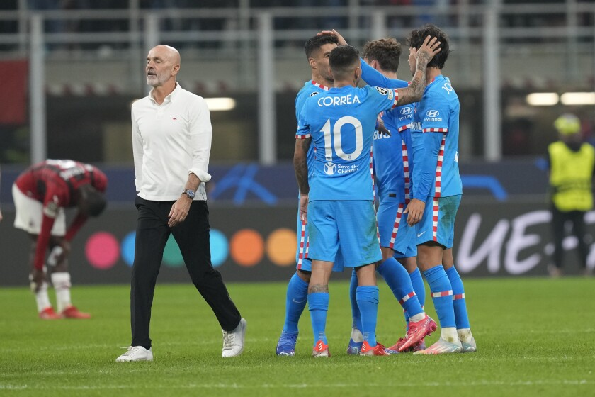 AC Milan's manager Stefano Pioli, left, walks past Atletico Madrid's players at the end of the Champions League group B soccer match between AC Milan and Atletico Madrid at the San Siro stadium in Milan, Italy, Tuesday, Sept. 28, 2021. (AP Photo/Antonio Calanni)
