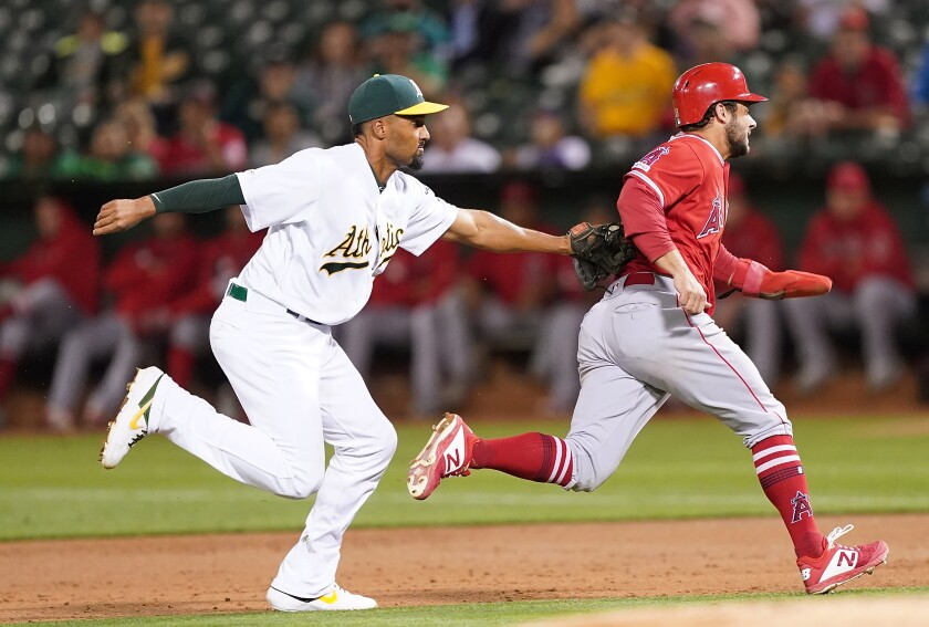 Oakland Athletics shortstop Marcus Semien tags out Angels baserunner David Fletcher during the third inning of the Angels' 7-5 loss Tuesday.