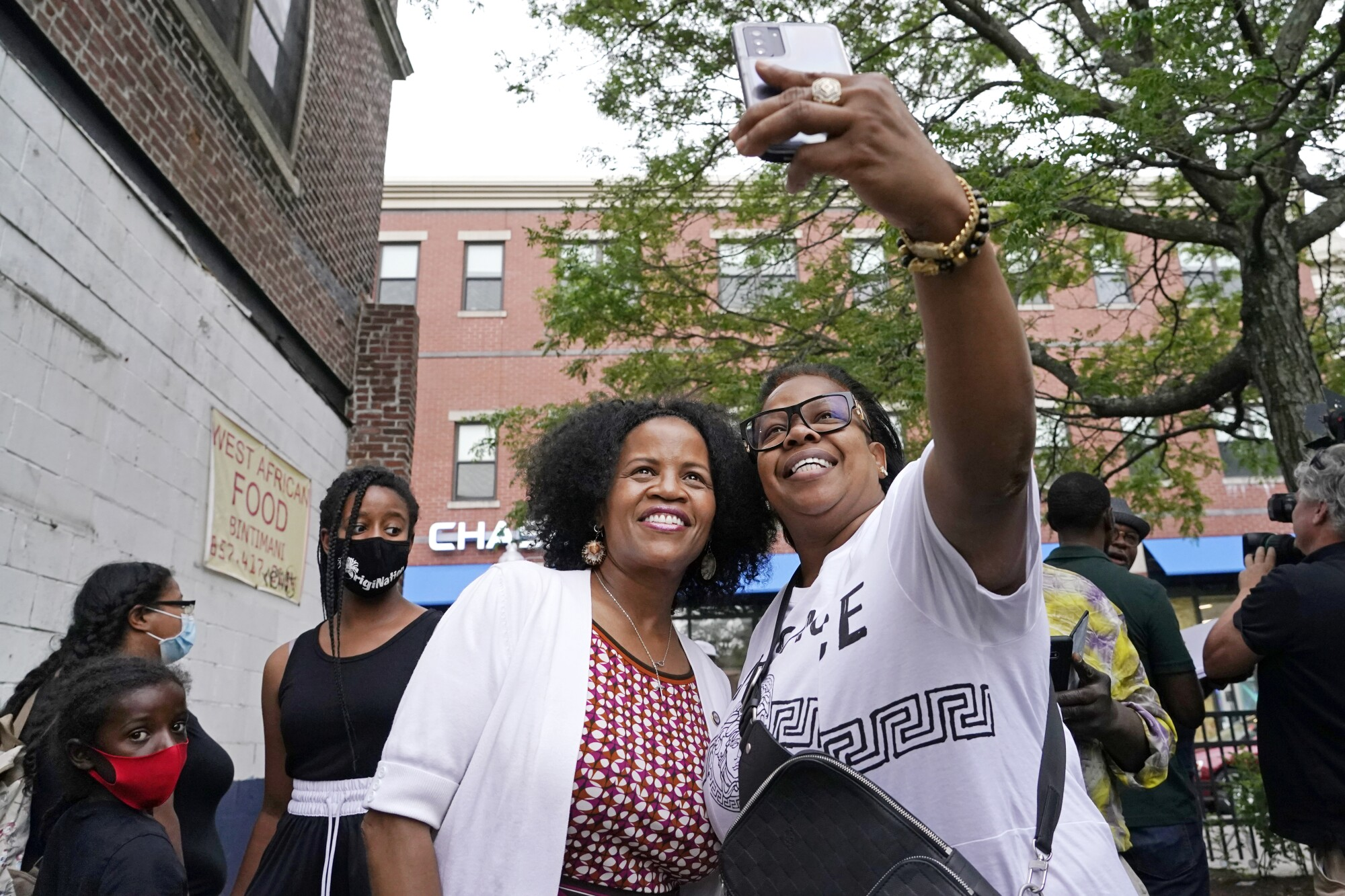 Boston's acting Mayor Kim Janey, left, takes a selfie with Mikey Miles as she meets people in Boston's Nubian Square.