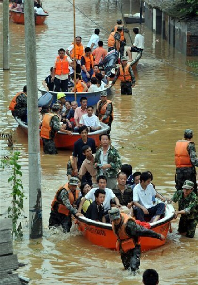 FILE - In this June 23, 2010 file photo released by China's Xinhua News Agency, armed police help residents evacuating from flooded area in Fuzhou city, central China's Jiangxi Province. More than 42 million people were forced to flee their homes because of natural disasters around the world in 2010, more than double the number during the previous year, experts said Monday, June 6, 2011. (AP Photo/Xinhua, Zhang Wu, File) NO SALES