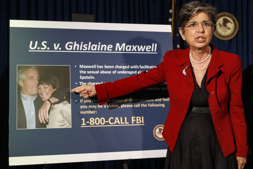 """FILE- In this July 2, 2020 file photo, Audrey Strauss, Acting United States Attorney for the Southern District of New York, points to a photo of Jeffrey Epstein and his ex-girlfriend Ghislaine Maxwell. Sex trafficking charges were added Monday, March 29, 2021 to the indictment against financier Jeffrey Epstein's ex-girlfriend as prosecutors alleged that she groomed a 14-year-old girl to recruit other young females in the early 2000s to provide """"sexualized massages"""" to Epstein in return for cash. (AP Photo/John Minchillo, File)"""