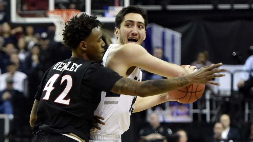Aztecs guard Jeremy Hemsley hounds Utah State's Abel Porter on Saturday during the Mountain West championship game at the Thomas & Mack Center in Las Vegas.