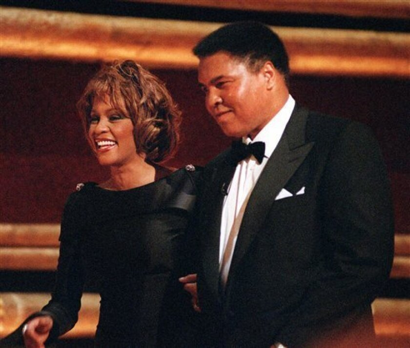 """FILE - In this Oct. 21, 1998 file photo, former World Heavyweight Boxing Champion Muhammad Ali is greeted by singer Whitney Houston as he arrives on stage at New York's Radio City Music Hall to accept a GQ """"Men of the Year"""" Award. Whitney Houston, who reigned as pop music's queen until her majestic voice and regal image were ravaged by drug use, has died, Saturday, Feb. 11, 2012. She was 48. (AP Photo/Mitch Jacobson, File)"""