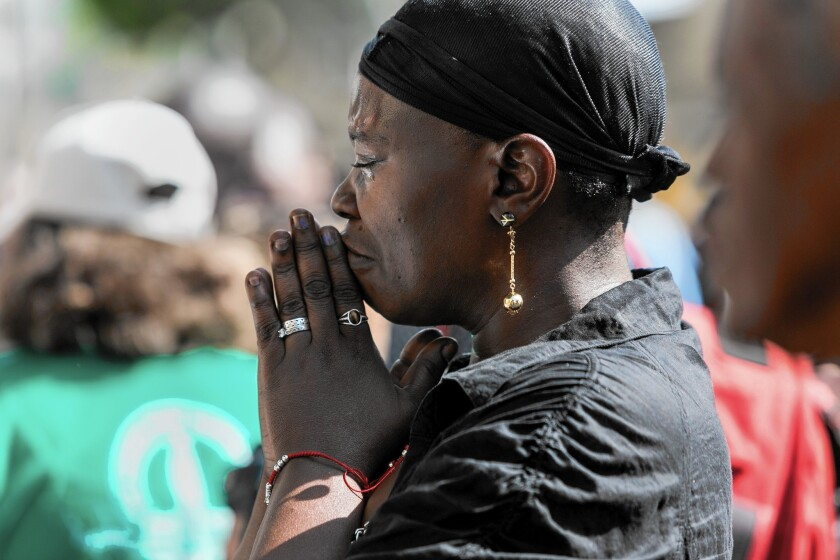 A woman weeps during a public memorial for Charley Leundeu Keunang, a homeless man shot and killed during a struggle with the LAPD on skid row.