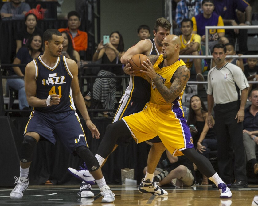 Lakers center Robert Sacre struggles for the ball against Utah center Jeff Withey (24) during overtime of a preseason game against the Jazz on Oct. 6.