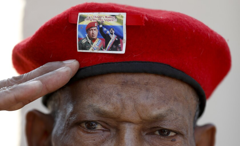 Un hombre con la emblemática boina roja del difunto presidente de Venezuela Hugo Chávez, adornada con una foto del actual presidente Nicolás Maduro con Chávez, saluda mientras espera para visitar los restos del líder en el sexto aniversario de su muerte, en esta fotografía de archivo del 5 de marzo de 2019, en Caracas. (AP Foto/Eduardo Verdugo)