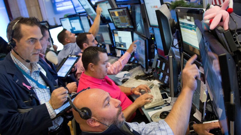 Members of Livermore Trading Group monitoring stock prices at the New York Stock Exchange on July 22.
