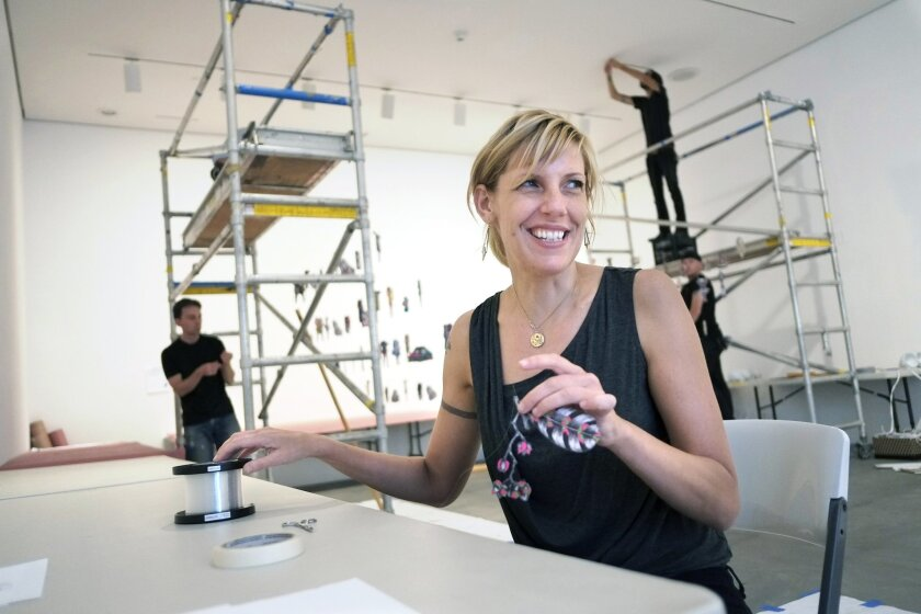 """Artist Margaret Noble attaches fishing line to paper dolls that will then be hung in f her exhibit """"44th and Landis"""" at  the Museum of Contemporary Art San Diego.  The exhibit is based largely on Noble's experience growing up in City Heights."""