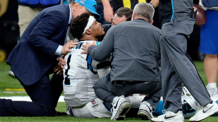 Cam Newton, quarterback de los Panthers de Carolina, recibe atención tras ser capturado en el partid