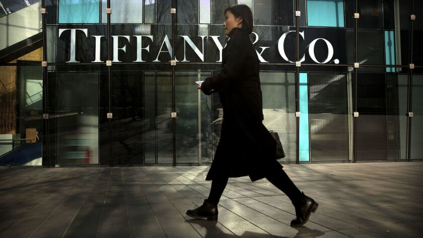 In this Thursday, Nov. 29, 2018, photo, a woman walks past a Tiffany & Co. store at a shopping mall