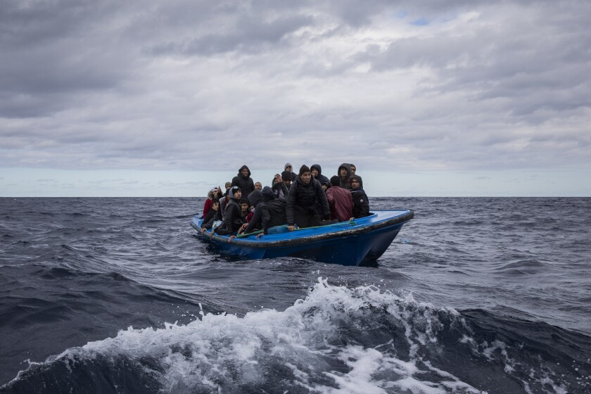 Men from Morocco and Bangladesh look out from an overcrowded wooden boat, as aid workers of the Spanish NGO Open Arms approach them in the Mediterranean Sea, international waters, off the Libyan coast, Friday, Jan. 10, 2020. (AP Photo/Santi Palacios)