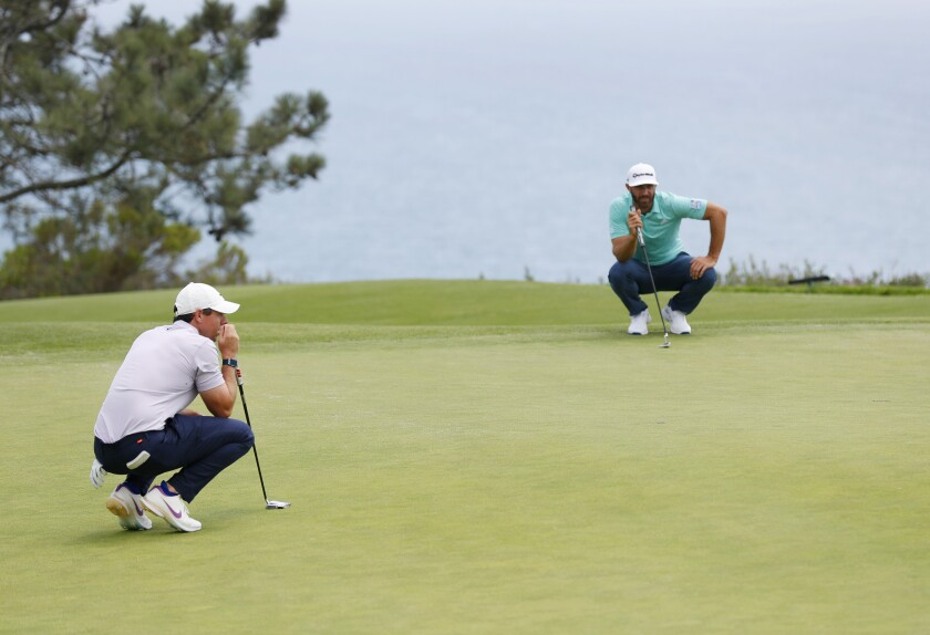 Rory McIlroy (left) and Dustin Johnson line up putts on fourth hole at Torrey Pines South during Wednesday's practice round.
