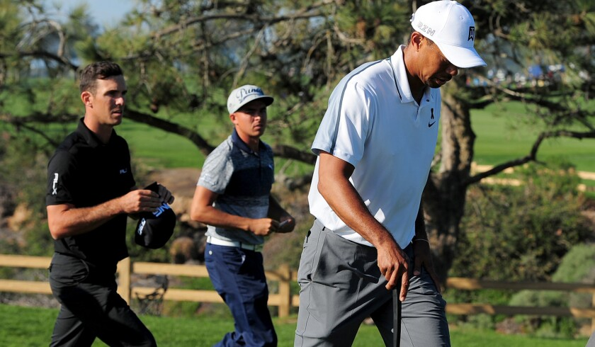 Tiger Woods walks off Torrey Pine Golf Course after withdrawing from the Farmers Insurance Open because of a back injury on Thursday.