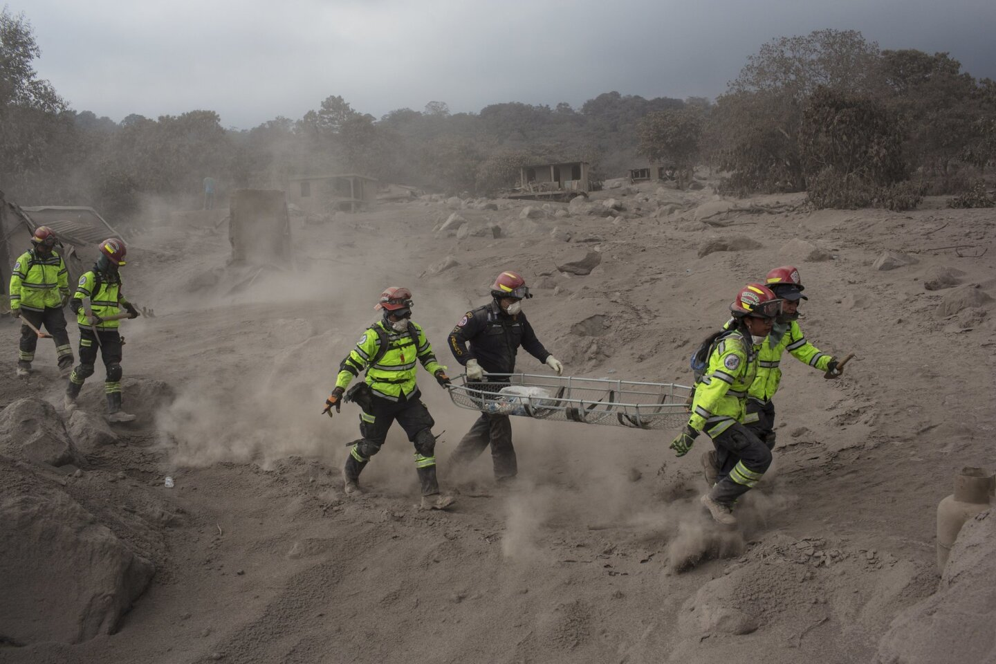 Rescue workers run for cover as the Fuego volcano in Guatemala blows more clouds of ash in the El Rodeo hamlet of Escuintla, Guatemala.