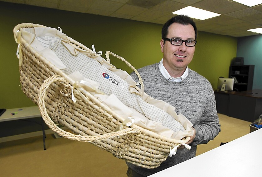 Ryan Farnsworth, executive director of Forever Footprints, holds one of the special Moses baskets for hospitals used to carry babies who are lost in pregnancy or stillborn.
